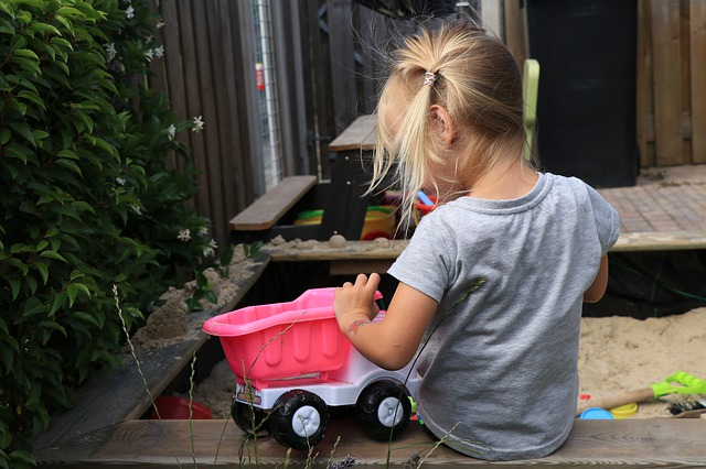 Holčička hrající si s růžovým autem