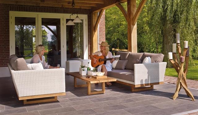 dvě ženy sedí na terase, zastřešené, jedna má v rukou kytaru a hraje, druhá drží skleničku se šampaňským